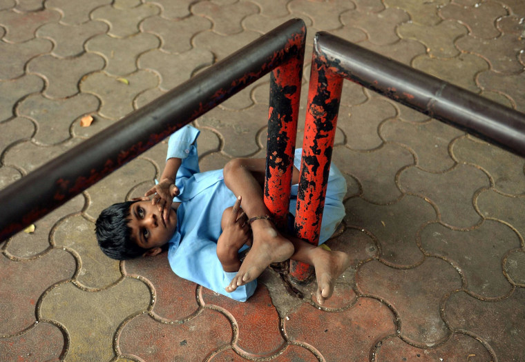 Image: Indian boy Lakhan Kale is tied with a cloth rope around his ankle, to a bus-stop pole in Mumbai.