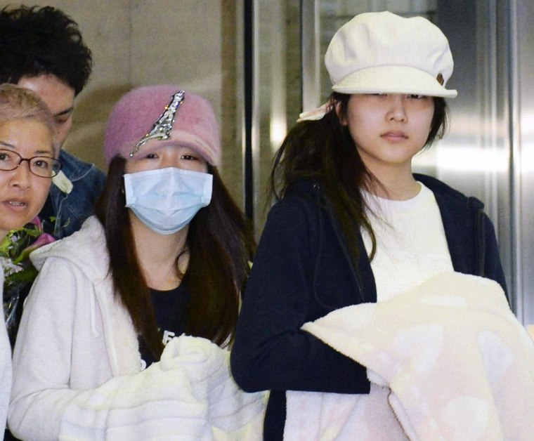 Image: Rina Kawaei, second right, and Anna Iriyama, right, two members of Japan's hugely popular female pop group AKB48, leave a hospital