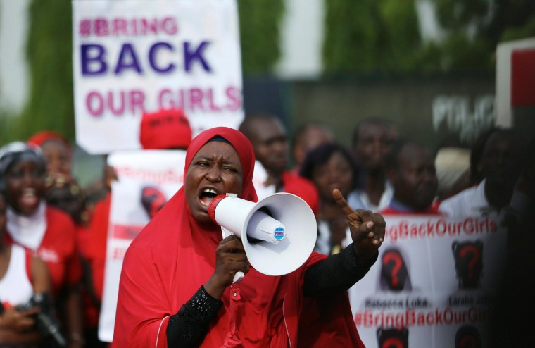 """Image: A protester addresses the \""""Bring Back Our Girls\"""" protest group as they march to the presidential villa"""