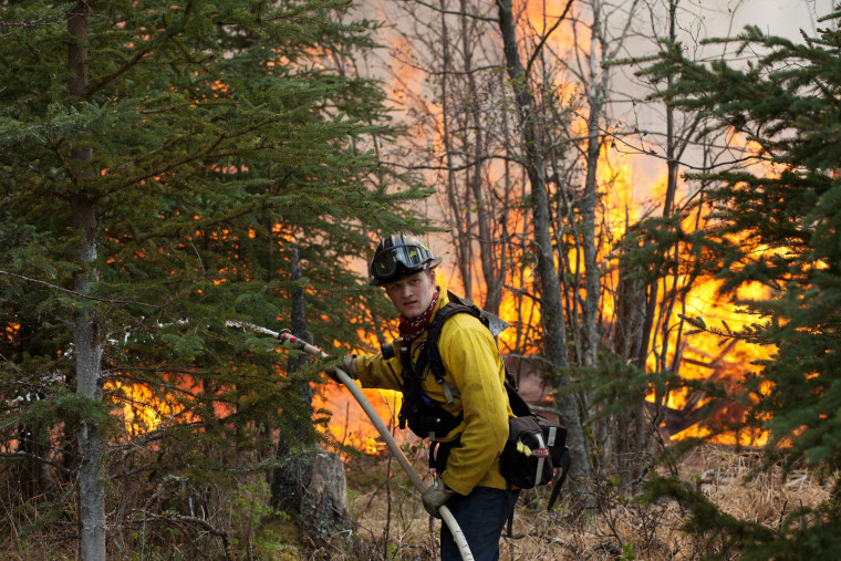 Image: Central Emergency Services firefighter Spencer Mclean works to contain a portion of a wildfire near the Funny River neighborhoo