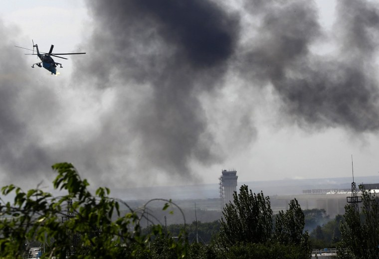 Image: A Ukrainian helicopter Mi-24 gunship fires its cannons against rebels at the main terminal building of Donetsk international airport