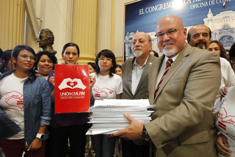 Image: Congressman Bruce poses for a picture holding signatures supporting the Civil Union project law at Peru's Congress in Lima