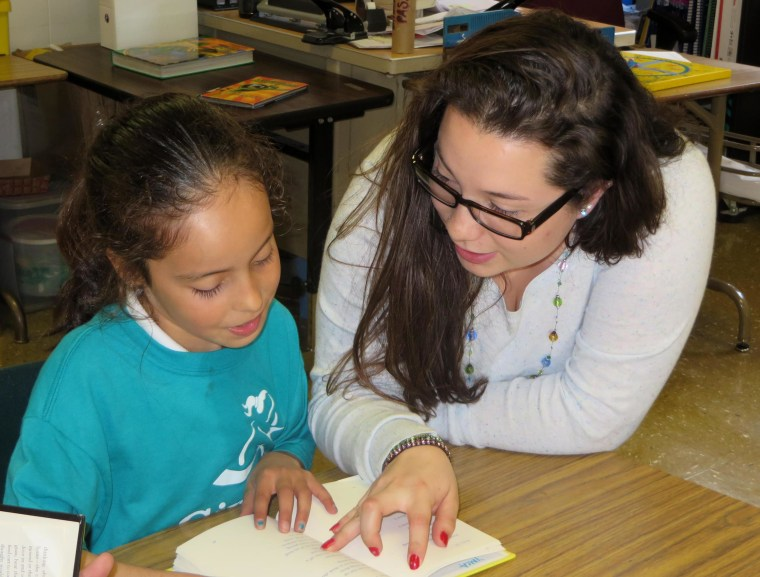 College student Priscila Trejo-Martinez, who was part of Mission Graduates' College Connect program as a high school student, now works as a Mission Graduates Program Assistant and is seen here reading aloud with Marshall 4th grader Joselyn.