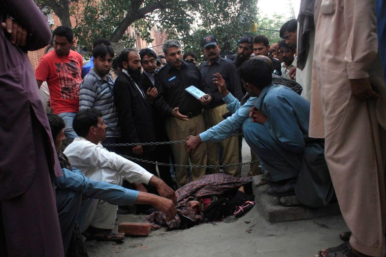 Police collect evidence near the body of Farzana Iqbal, who was killed by family members, at the site near the Lahore High Court building in Pakistan Tuesday.