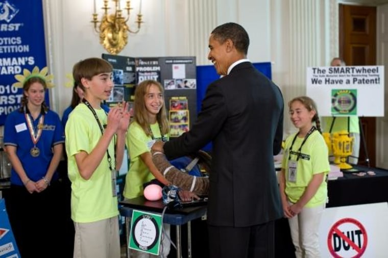 President Obama grabs the SmartWheel as TJ Evarts and the team explain the invention.