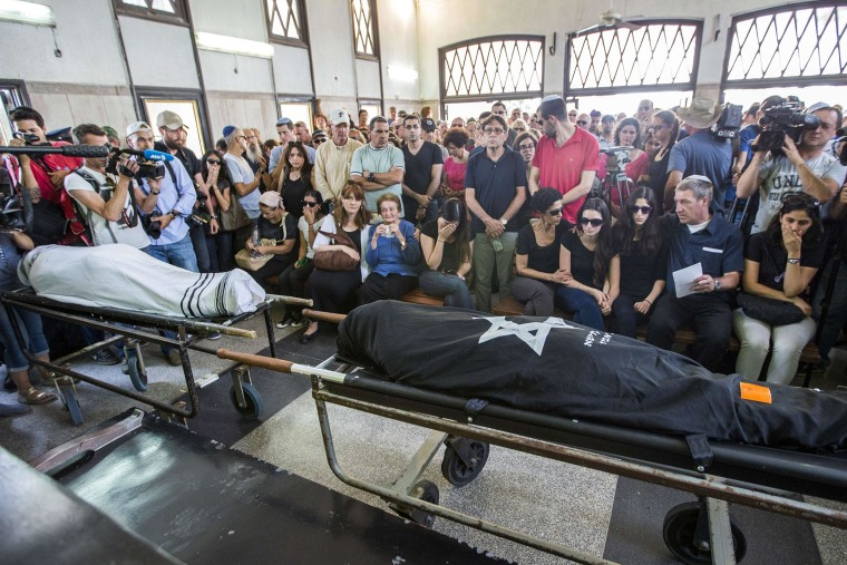 Image: Relatives mourn over the bodies of Emanuel and Miriam Riva on Tuesday