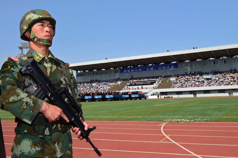 Image: A paramilitary policeman stands guard near trucks carrying criminals and suspects during a mass sentencing rally at a stadium in Yili