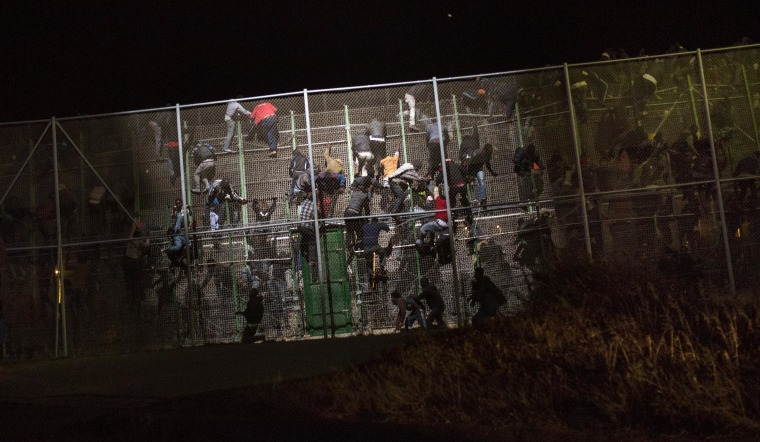 Image: Sub-Saharan migrants scale a metallic fence that divides Morocco and the Spanish enclave of Melilla