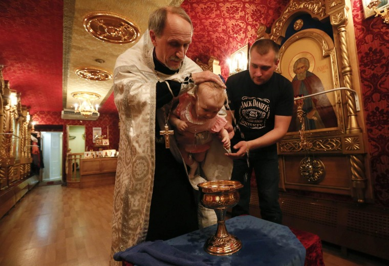 Image: An Orthodox priest baptizes a baby at a church inside the Doctor Voino-Yasenetsky Saint Luka train at a railway station of Divnogorsk