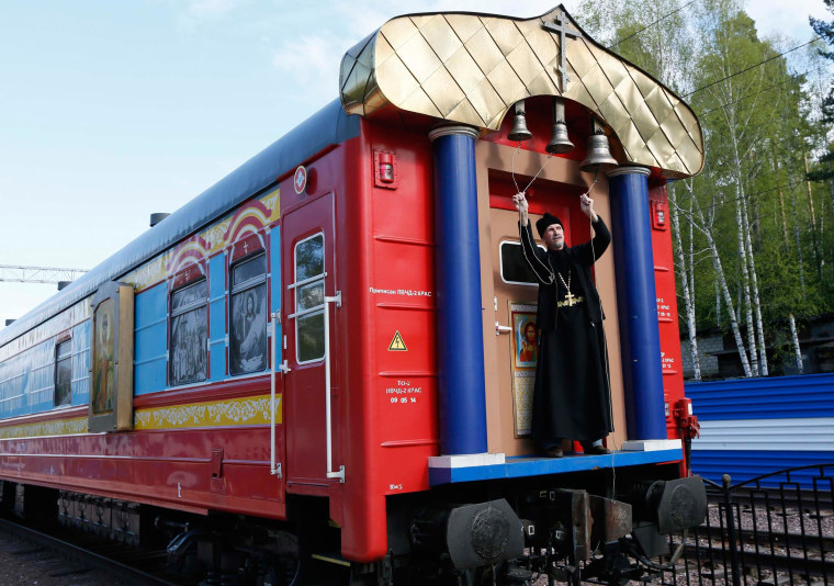 An Orthodox priest rings bells outside a train carriage serving as a mobile church, at a railway station in Divnogorsk, Russia, on May 26, 2014.