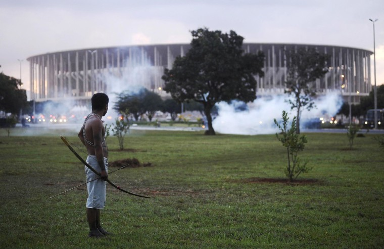 Image: Native Brazilian stands in front of the  Mane Garrincha soccer stadium as police use tear gas in Brasilia