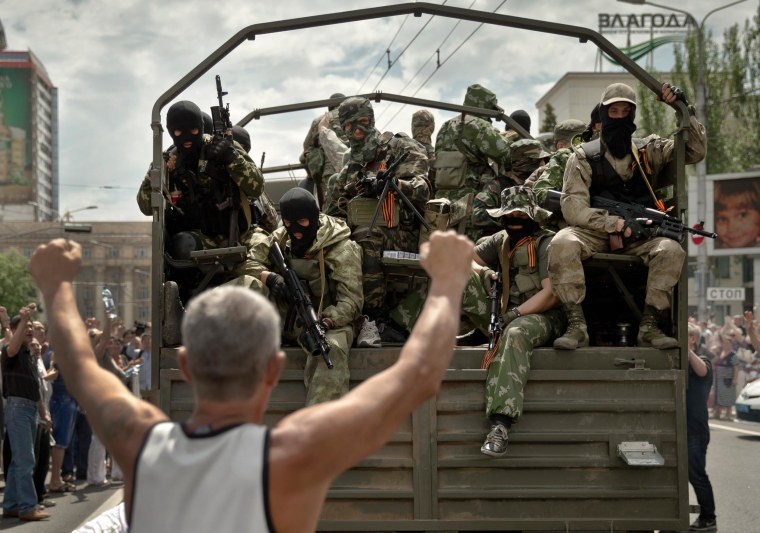 Image: A man cheers as pro-Russian gunmen drive away in a truck in Lenin square in Donetsk, Ukraine