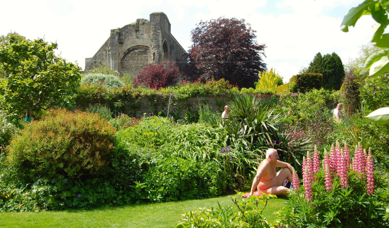 Nudists relax at Abbey House Gardens in Malmesbury, U.K.