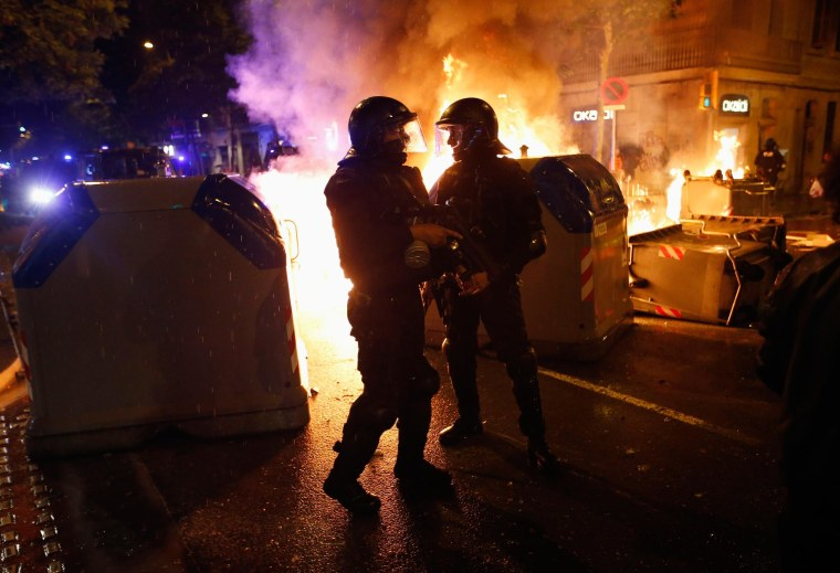 Image: Police stand next to burning containers during a protest against the eviction of squatters from Can Vies building at Sants neighbourhood