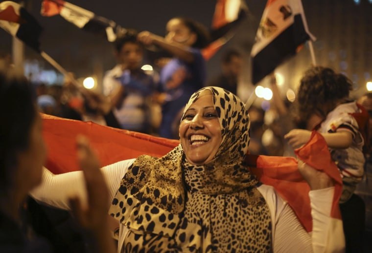 Image: A supporter holds an Egyptian flag while celebrating at Tahrir Square in Cairo