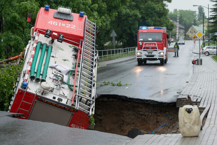 A fire truck fell into a cavity that opened up in a road after heavy overnight rain in Glucholazy, in lower Silesia, Poland, on May 29, 2014.