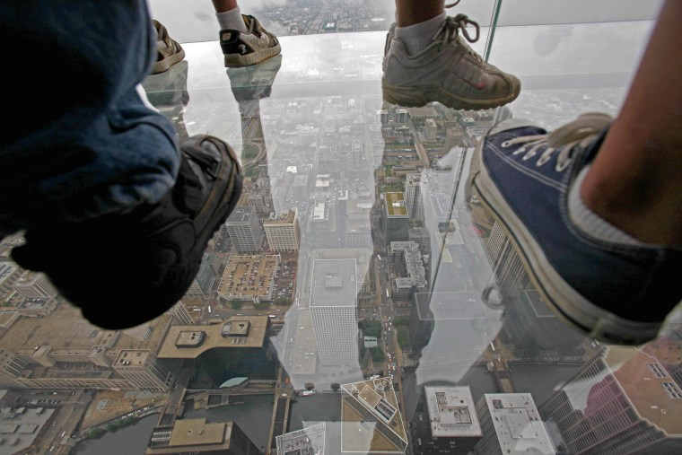 "Visitors stand on ""The Ledge,"" a glass balcony suspended 1,353 feet (412 meters) in the air from the Willis Tower's 103rd floor Skydeck."