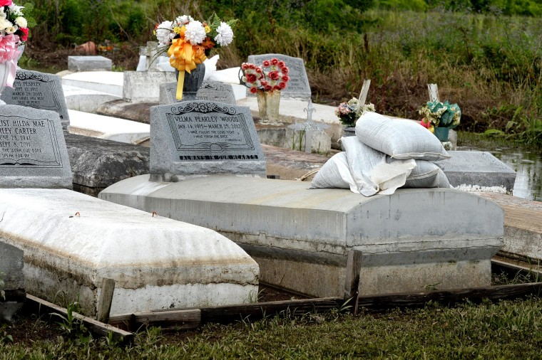 Image: Sandbags sit on top of graves for weight in the Rosehill Baptist and St. James United Methodist churches cemetery