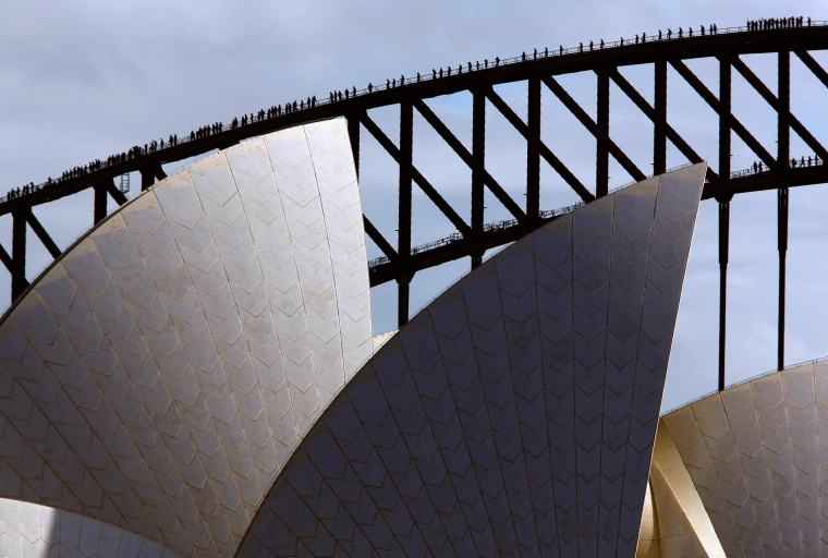 Climbers walk along the arch of Sydney Harbor Bridge behind the Sydney Opera House on May 30, 2014 as they attempt to break the record for the most number of people on the arch of the famous bridge at the same time.