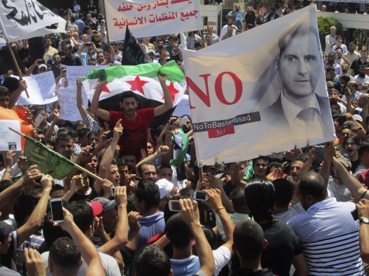 Image: Lebanese protesters join Syrian refugees opposing Syria's President al-Assad as they hold flags and chant slogans during demonstration against participation of the Syrian refugees in the Syrian election in Lebanon, after their Friday prayers in Tri