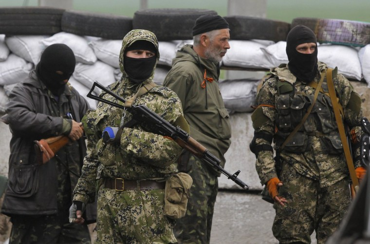 Pro-Russian masked armed militants guard barricades near Slovyansk, eastern Ukraine, on April 30, 2014.