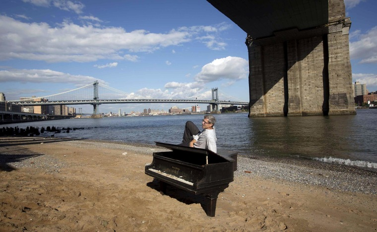 A man poses for a photo on a grand piano that has been left by the East River underneath the Brooklyn Bridge in the Manhattan borough of New York May 31.