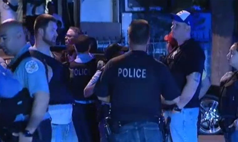 Image: Police stand near the scene of a shooting in Chicago.