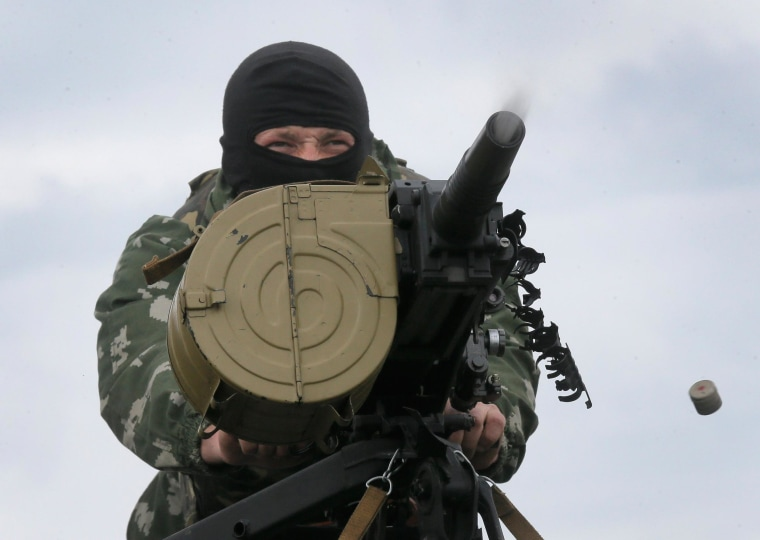 Image: A Ukrainian soldier shoots from a grenade launcher