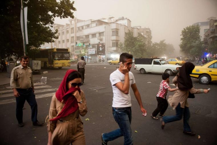 Image: Iranians walk amidst dust as a sandstorm engulfs the capital Tehran on Monday