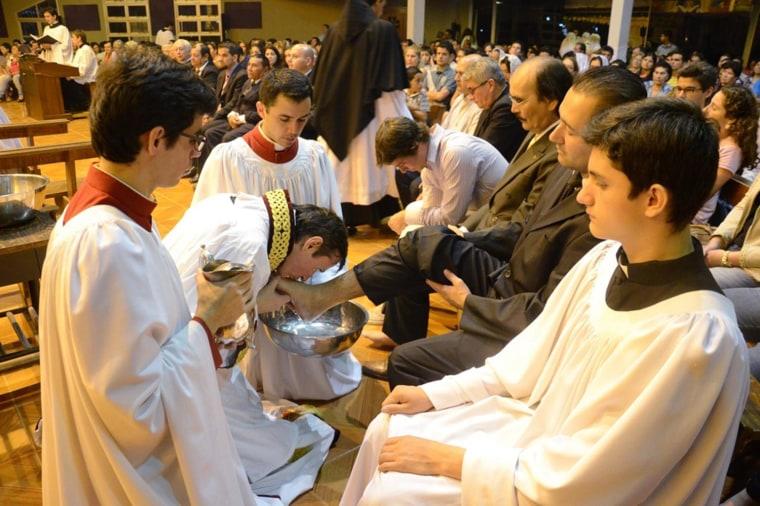 Priest Carlos Urrutigoity kisses the feet of the faithful.
