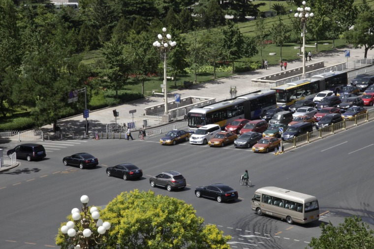Image: A convoy of cars drive across Beijing's Changan Blvd., near Tiananmen Square