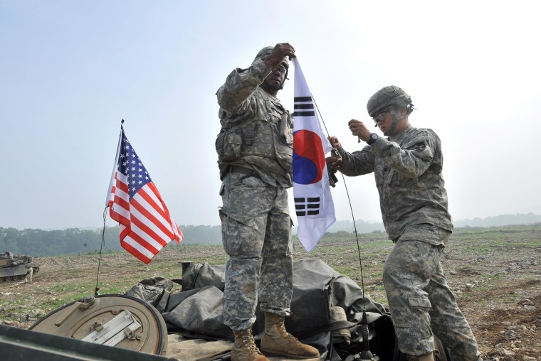 U.S. soldiers from 2nd Infantry Division hang a South Korean flag on the top of their M1A2 tank