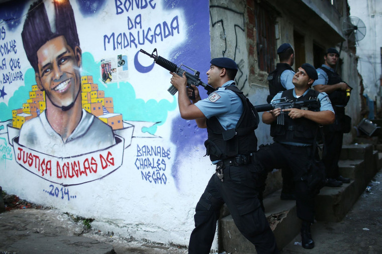 Image: Police patrol next to a mural of dancer Douglas Rafael da Silva Pereira in the pacified Pavao-Pavaozinho community