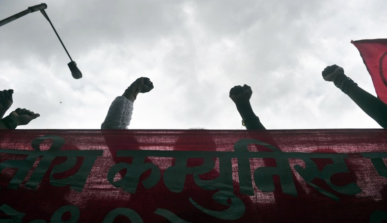 Image: Indian demonstrators raise clenthed fists as they protest the killing of a leading Indian anti-superstition activist on Aug. 21, 2013
