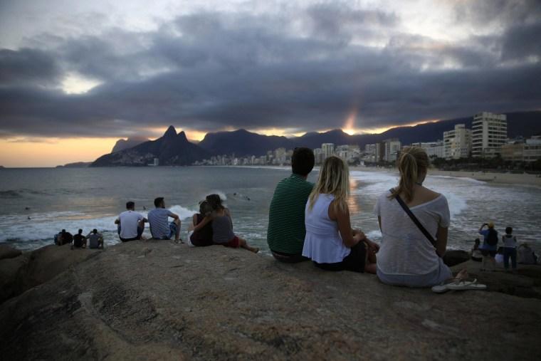 Image: People enjoy the sunset on Copacabana beach on Tuesday in Rio de Janeiro, Brazil.