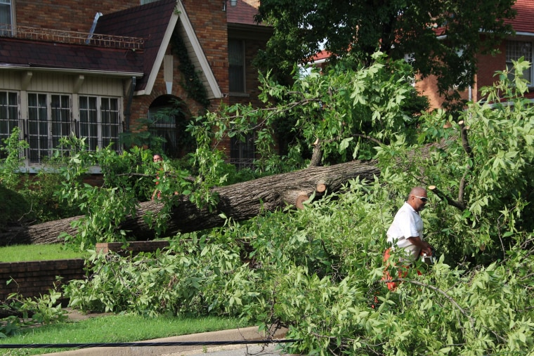 Image: A maintenance worker for Craighead Park, cuts the limbs off a fallen tree that took out a power line on the corner of McClure and Washington in Jonesboro, Ark.