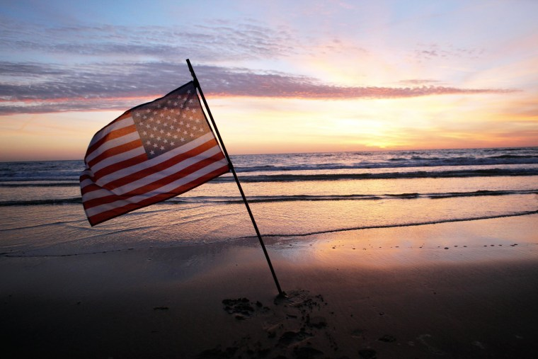 Image: An American flag is placed in the sand of Omaha Beach, western France