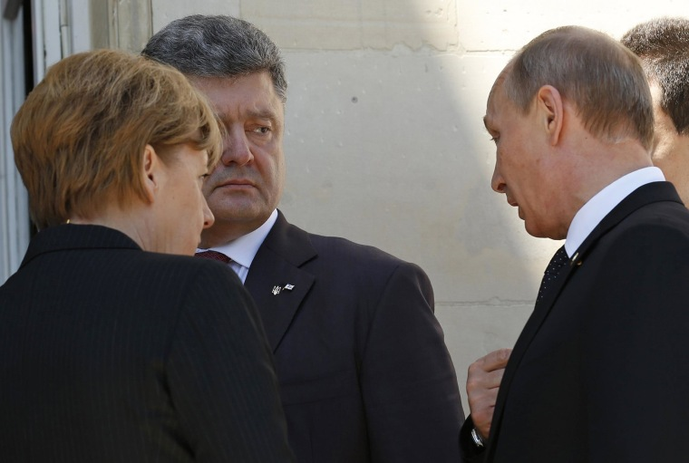 Ukraine president-elect Petro Poroshenko, second from left, German Chancellor Angela Merkel and Russian President Vladimir Putin talk after a group photo during the 70th anniversary of the D-Day landings in Benouville, France, on June 6, 2014.