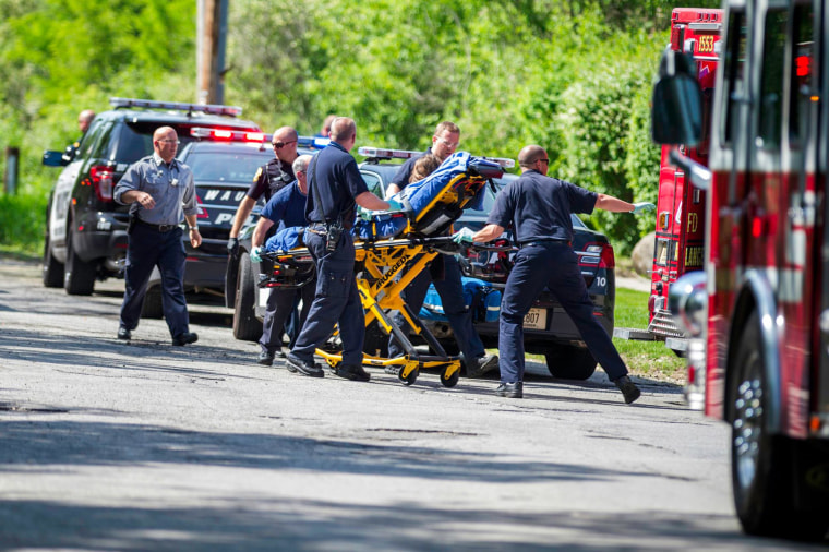 Image: Rescue workers take a stabbing victim to the ambulance in Waukesha, Wis.
