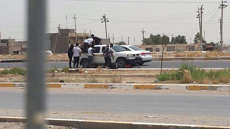 Image: Students of Anbar university ride on the back of a truck as they leave the university building in Ramadi city