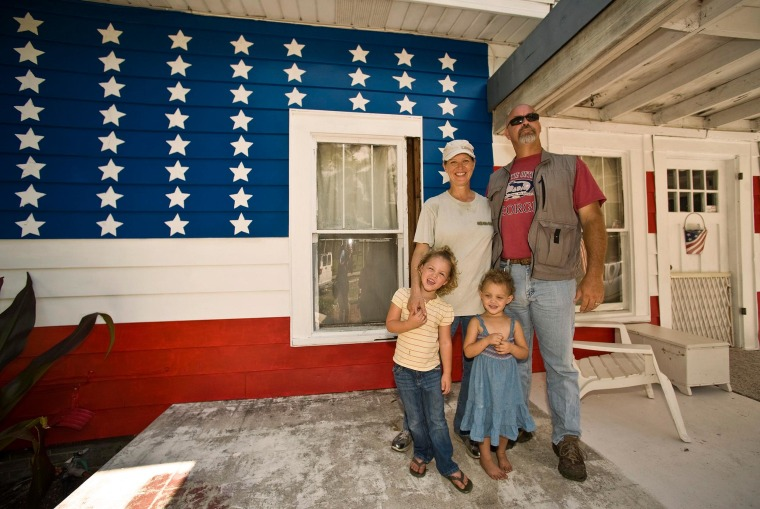 Image: Greer and his wife stand with daughters on the front porch of their 110-year-old house in Bradenton