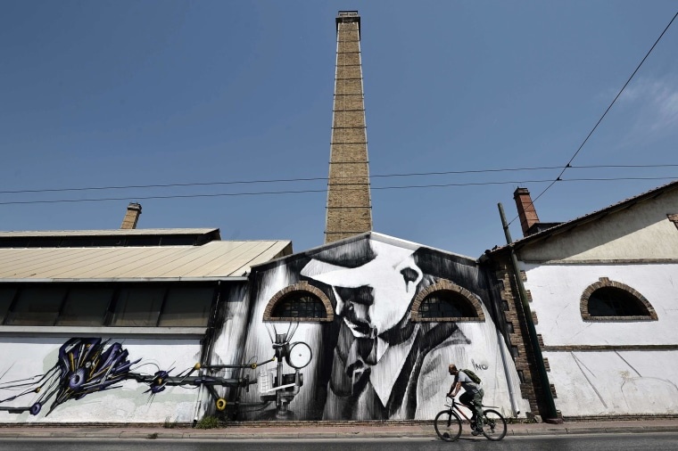 Image: A man rides by a new mural by INO at the Athens Technopolis, an industrial museum and a major cultural venue