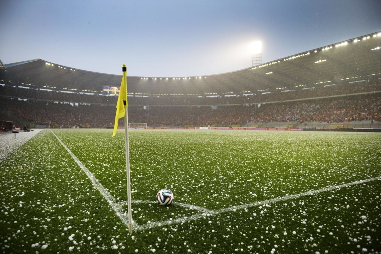 Image: Hail lays on the pitch during a friendly football game between the Belgian national soccer team, the Red Devils and Tunisia
