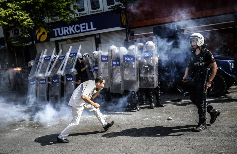Image: A man runs in front of Turkish riot policemen during a demonstration by Kurdish protesters