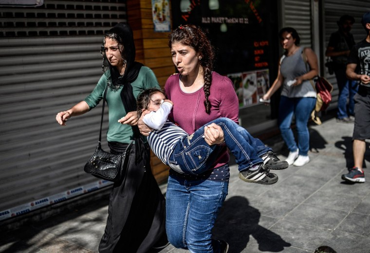 Image: A woman carries a young girl suffering the effects of tear gas