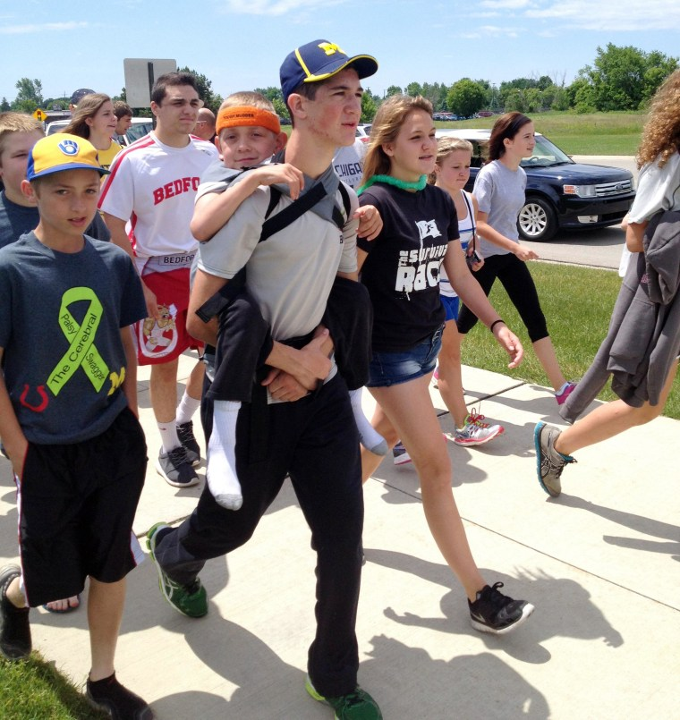 "Image: Hunter Gandee, 14, walks in Saline, Mich., on Sunday, during the second day of his two-day, 40-mile ""Cerebral Palsy Swagger"" walk"