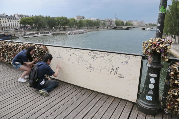 Image: People write inscriptions onto a wooden panel on the Pont des Arts bridge