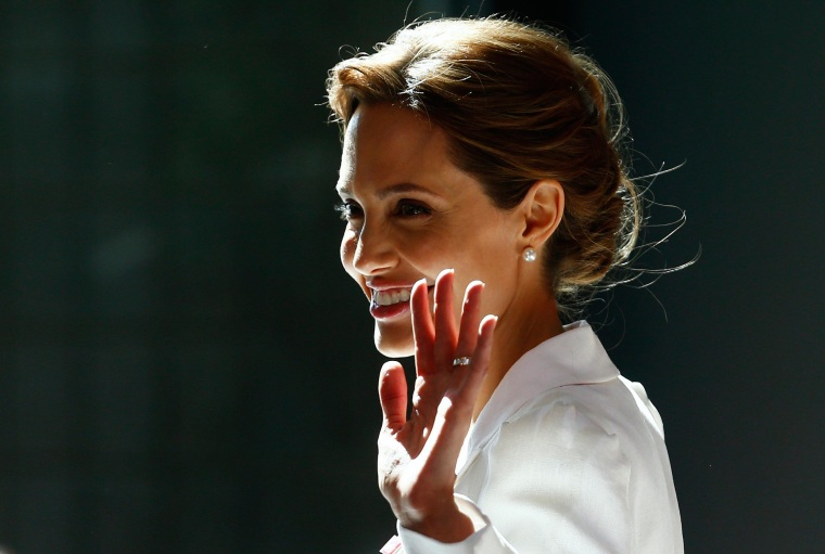Image:  Angelina Jolie waves as she arrives at a global summit to end sexual violence in conflict, in London