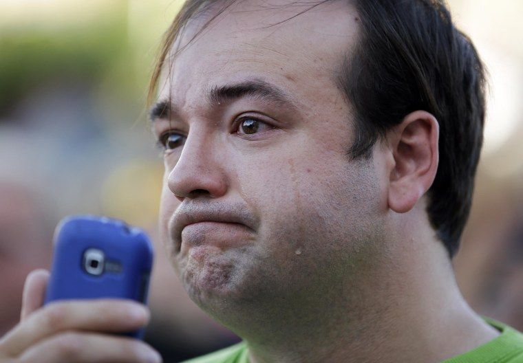 Image: Steven Carver cries while attending a vigil near CiCi's Pizza