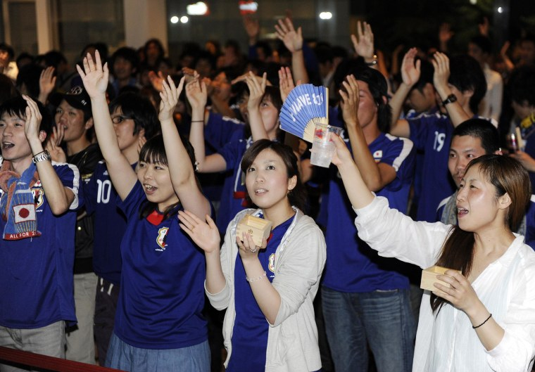 Image: Japanese football fans in national team uniforms cheer before the start of the 2010 World Cup match between Japan and Cameroon at a sports bar in Tokyo